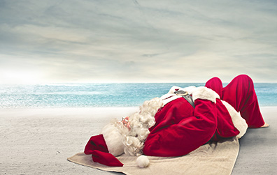 Santa relieving stress by lying on the beach